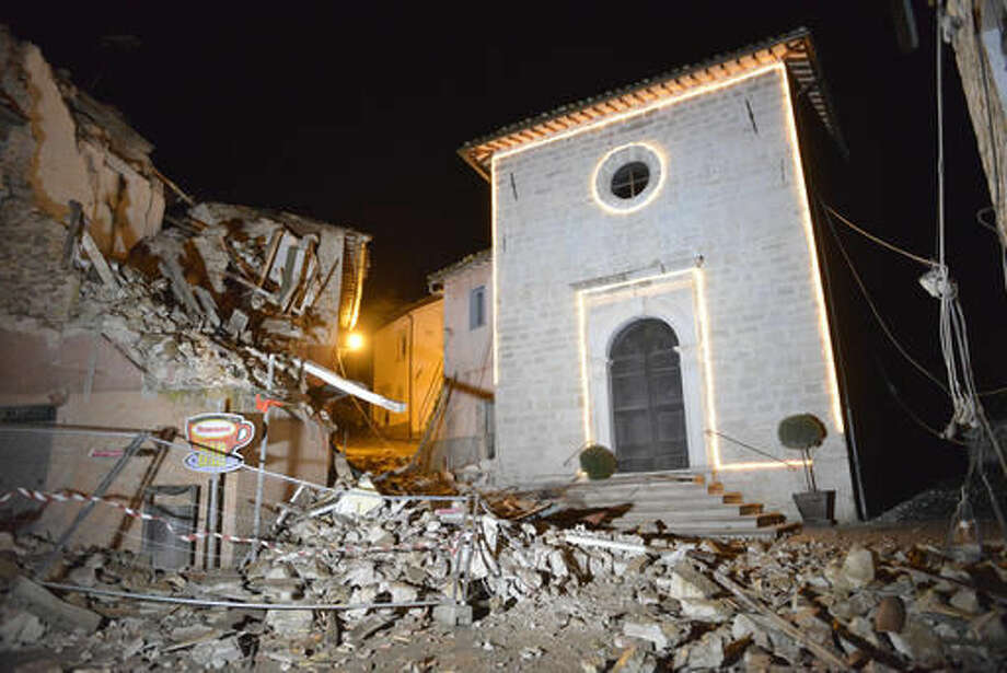 The Church of San Sebastiano stands amidst damaged houses in Castelsantangelo sul Nera, Italy, Wednesday, Oct 26, 2016 following an earthquake,. A pair of strong aftershocks shook central Italy late Wednesday, crumbling churches and buildings, knocking out power and sending panicked residents into the rain-drenched streets just two months after a powerful earthquake killed nearly 300 people. (AP Photo/Sandro Perozzi)