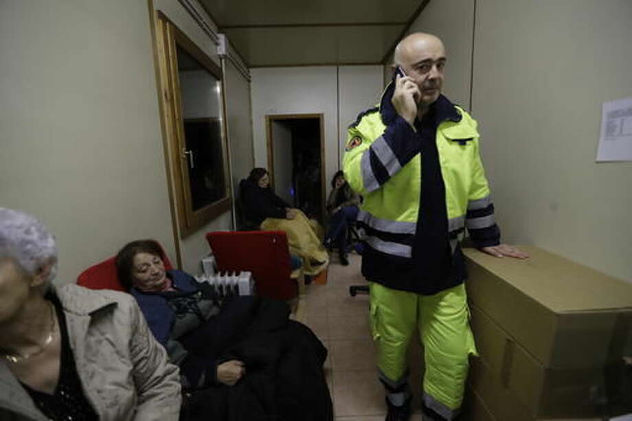 Mayor of Visso Giuliano Pazzaglini speaks over the phone in the offices of the Italian Red Cross in Visso, central Italy, crowded with residents, early Thursday, Oct 27, 2016, after a 5.9 earthquake destroyed part of their neighborhood. A pair of strong aftershocks shook central Italy late Wednesday, crumbling churches and buildings, knocking out power and sending panicked residents into the rain-drenched streets just two months after a powerful earthquake killed nearly 300 people. (AP Photo/Alessandra Tarantino)