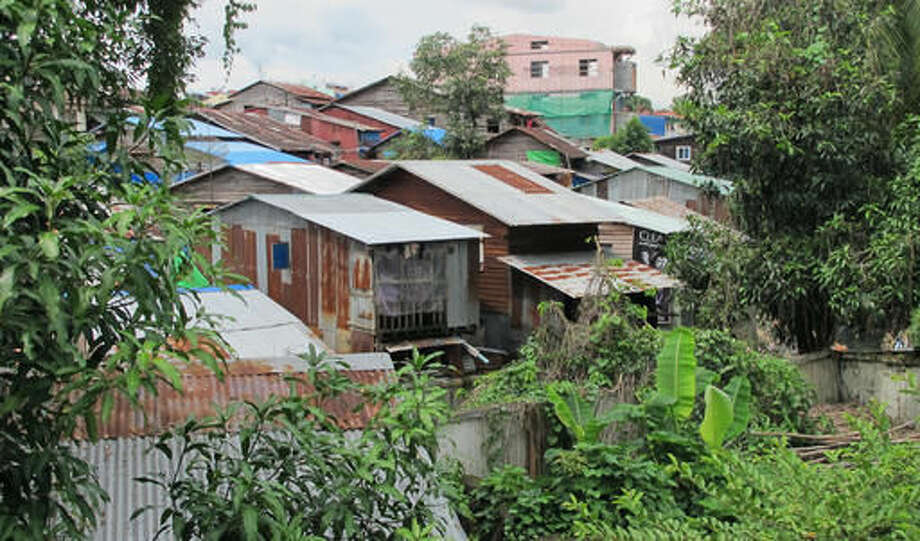 """This Oct. 6, 2016 photo shows typical houses in Yangon, Myanmar. The Yangon Heritage Trust says Myanmar's largest city and commercial capital is facing its """"last best chance"""" to salvage and restore many crumbling colonial treasures. They recently proposed a """"heritage strategy"""" for the city that outlines a vision of how to make the city more livable, modern and still affordable as property developers crowd in, while preserving its unique landmarks and neglected green spaces. (AP Photo/Elaine Kurtenbach)"""