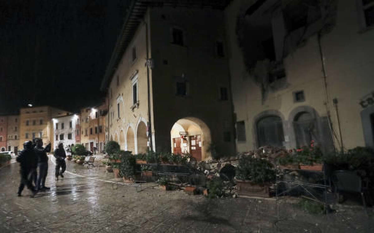 Rescuers and residents wander around the small town of Visso in central Italy, early Thursday, Oct 27, 2016, after a 5.9 earthquake destroyed part of their neighborhood. A pair of strong aftershocks shook central Italy late Wednesday, crumbling churches and buildings, knocking out power and sending panicked residents into the rain-drenched streets just two months after a powerful earthquake killed nearly 300 people. (AP Photo/Alessandra Tarantino)