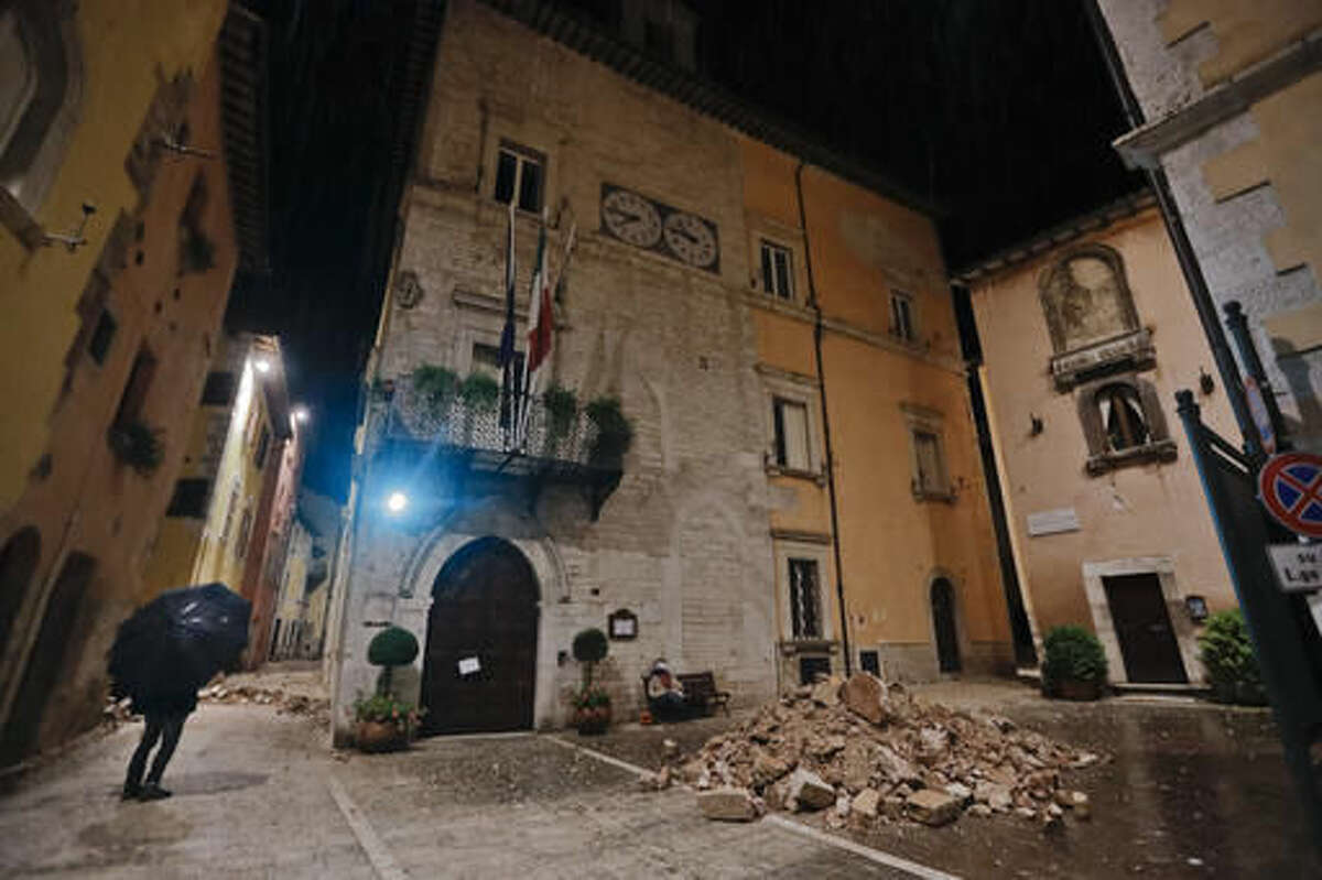 People wander around the small town of Visso in central Italy, early Thursday, Oct 27, 2016, after a 5.9 earthquake that destroyed part of their neighborhood. A pair of strong aftershocks shook central Italy late Wednesday, crumbling churches and buildings, knocking out power and sending panicked residents into the rain-drenched streets just two months after a powerful earthquake killed nearly 300 people. (AP Photo/Alessandra Tarantino)