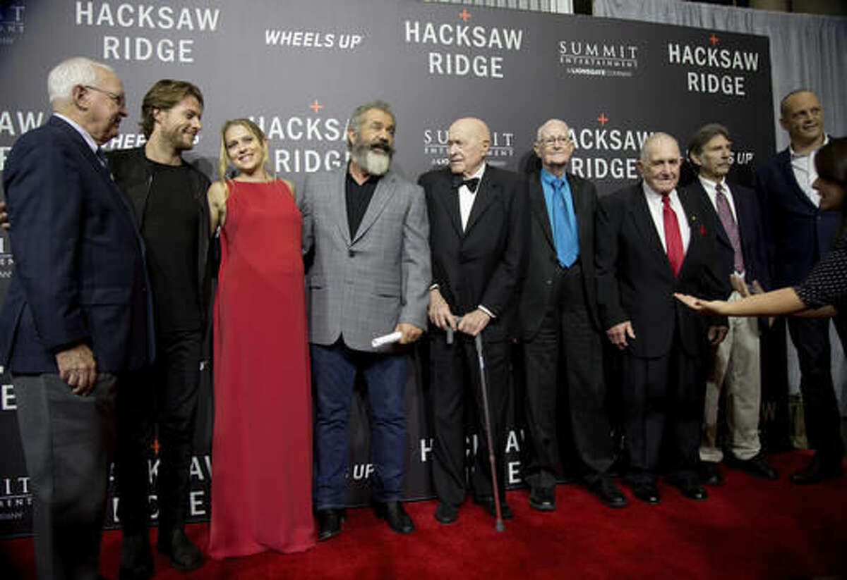 """Actor Luke Bracey, second from left, actress Teresa Palmer, director Mel Gibson, World War II veterans Joe Clapper, RV Burgin, Robert Akins, and Desmond Doss Jr. and actor Vince Vaughn pose on the red carpet at a screening of the movie """"Hacksaw Ridge,"""" at The National WWII Museum, in New Orleans, Wednesday, Oct. 26, 2016. The film depicts the life of conscientious objector and Congressional Medal of Honor recipient, Desmond Doss. (AP Photo/Max Becherer)"""