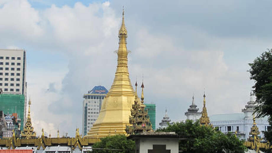 """In this Oct. 3, 2016 photo, a golden stupa stands in a temple compound surrounded by modern buildings in Yangon, Myanmar. The Yangon Heritage Trust says Myanmar's largest city and commercial capital is facing its """"last best chance"""" to salvage and restore many crumbling colonial treasures. They recently proposed a """"heritage strategy"""" for the city that outlines a vision of how to make the city more livable, modern and still affordable as property developers crowd in, while preserving its unique landmarks and neglected green spaces. (AP Photo/Elaine Kurtenbach)"""
