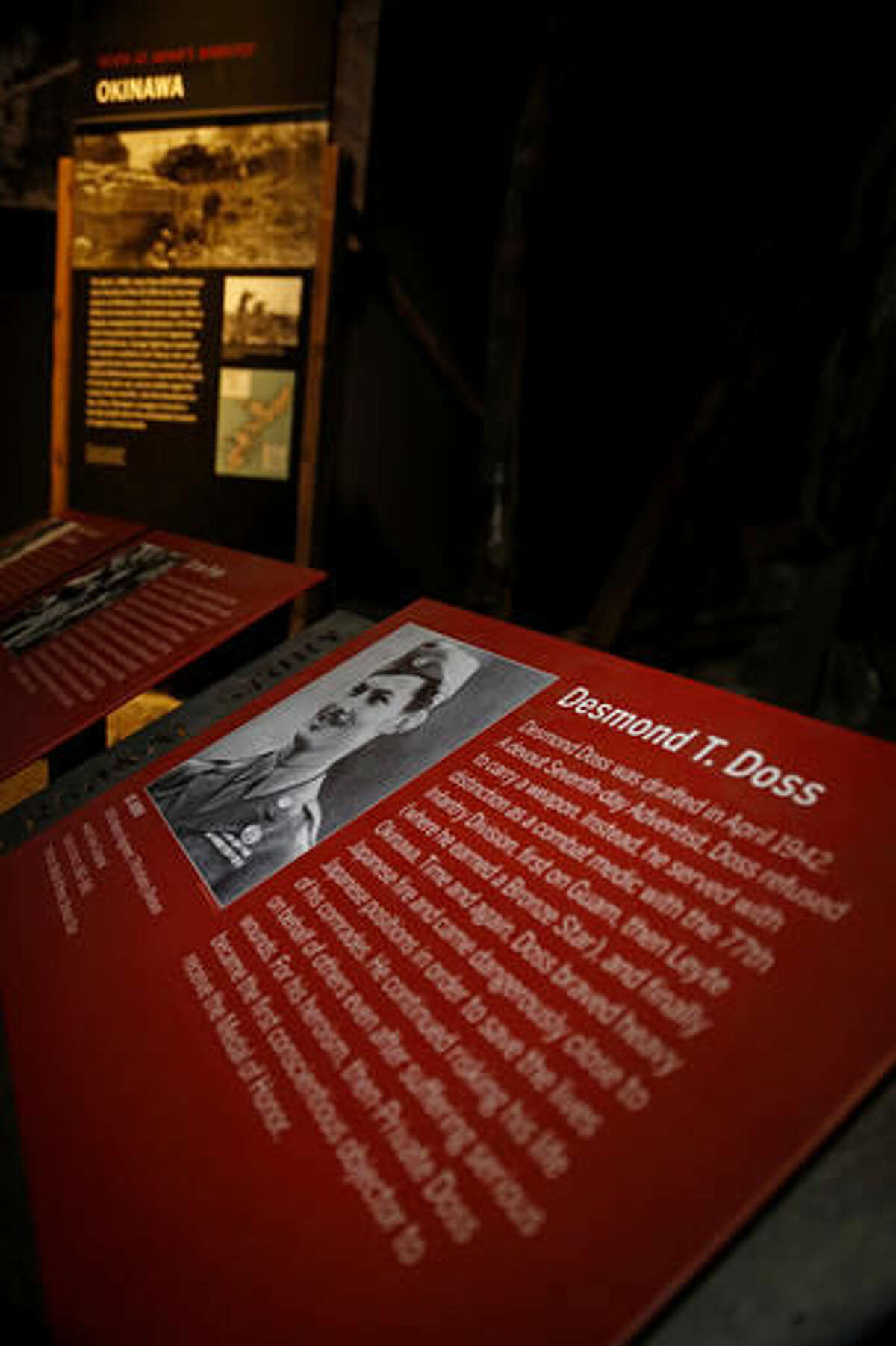 """A plaque describing the personal story of Congressional Medal of Honor recipient, Desmond Doss, is part of the Okinawa display at The National WWII Museum, in New Orleans, Wednesday, Oct. 26, 2016. The film """"Hacksaw Ridge,"""" directed by Mel Gibson, depicts the life of conscientious objector Desmond Doss. (AP Photo/Max Becherer)"""