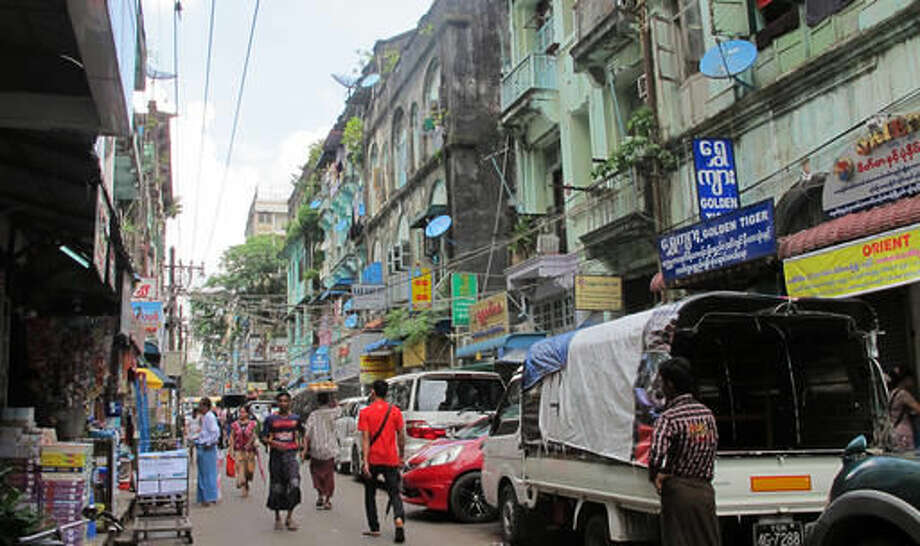 """In this Oct. 3, 2016 photo, people walk in a downtown shopping street lined with old colonial buildings used as shops, restaurants and houses in Yangon, Myanmar. The Yangon Heritage Trust says Myanmar's largest city and commercial capital is facing its """"last best chance"""" to salvage and restore many crumbling colonial treasures. They recently proposed a """"heritage strategy"""" for the city that outlines a vision of how to make the city more livable, modern and still affordable as property developers crowd in, while preserving its unique landmarks and neglected green spaces. (AP Photo/Elaine Kurtenbach)"""