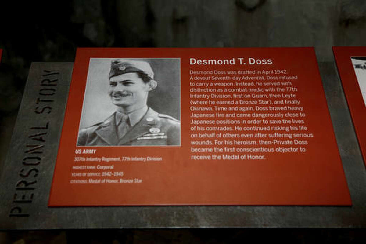 """A plaque describing the personal story of Congressional Medal of Honor recipient, Desmond Doss, is part of the Okinawa display at The National WWII Museum, in New Orleans, Wednesday, Oct. 26, 2016. The film """"Hacksaw Ridge,"""" directed by Mel Gibson, depicts the life of conscientious objector, Desmond Doss. (AP Photo/Max Becherer)"""