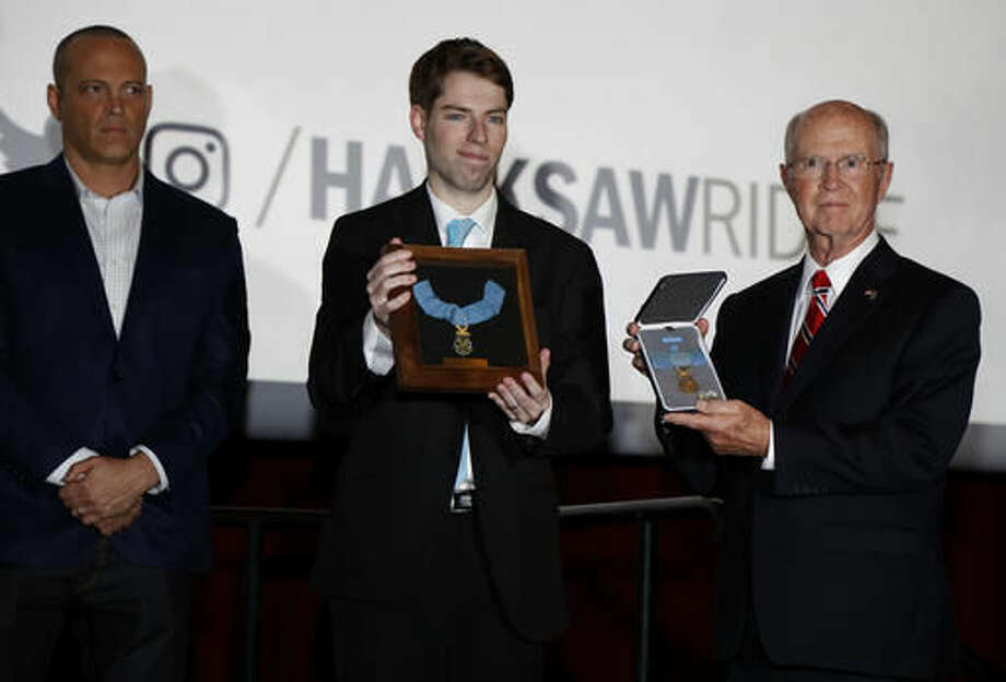 "Actor Vince Vaughn looks on as Charles Googe, center, and Dr. Charles Knapp, right, show two Congressional Medals of Honor given to Desmond Doss, at a screening of the movie ""Hacksaw Ridge,"" at The National WWII Museum, in New Orleans, Wednesday, Oct. 26, 2016. The film depicts the life of conscientious objector and Congressional Medal of Honor recipient, Desmond Doss. (AP Photo/Max Becherer)"