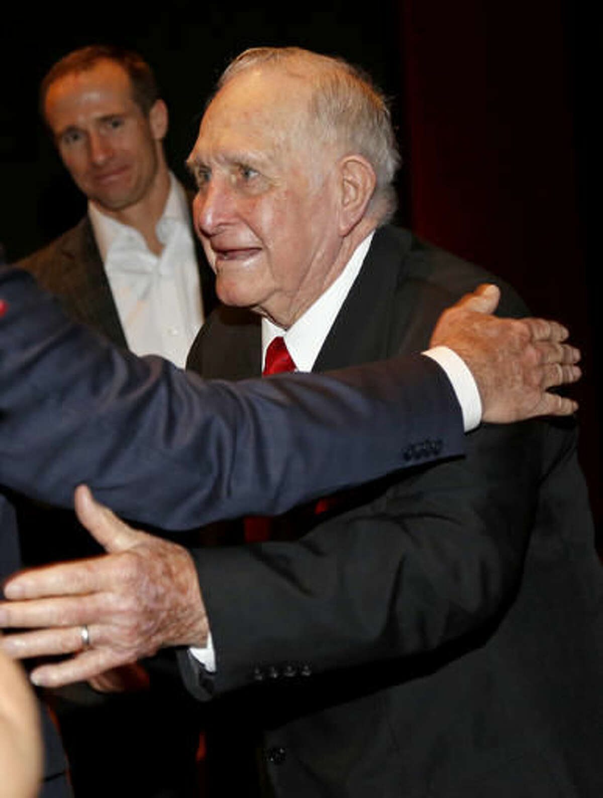 """World War II veteran Robert Akins is recognized by the audience during a screening of the movie """"Hacksaw Ridge"""" at The National WWII Museum, in New Orleans, Wednesday, Oct. 26, 2016. Akins is the grandfather of New Orleans Saints quarter back Drew Brees, seen in background. (AP Photo/Max Becherer)"""