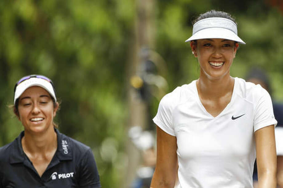 Michelle Wie, right, and Marina Alex, both of the United States shares a light moment as they approaches the seventh hole during the first round of the LPGA golf tournament at Tournament Players Club (TPC) in Kuala Lumpur, Malaysia, Thursday, Oct. 27, 2016. (AP Photo/Joshua Paul)