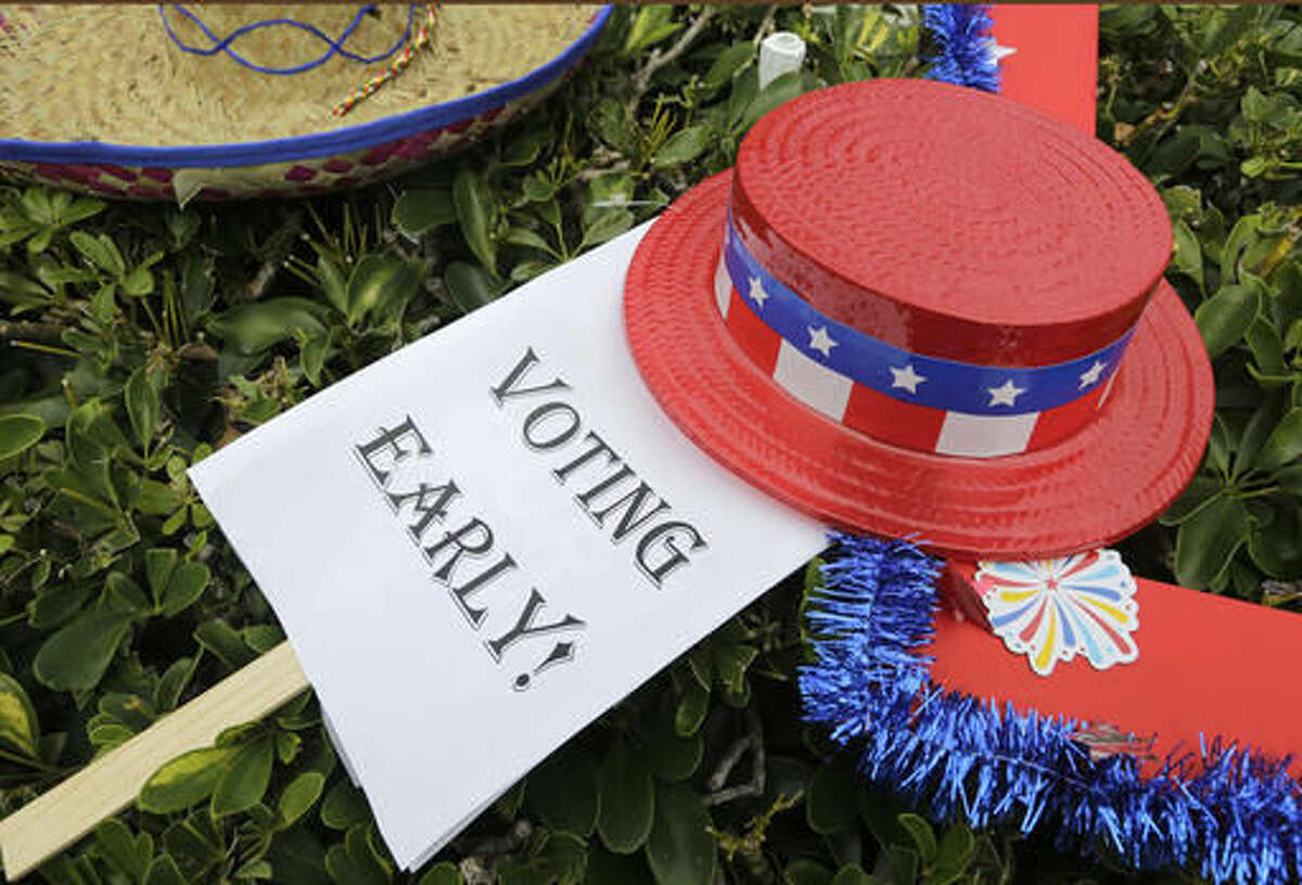 In this Oct. 24, 2016, photo, an early voting sign is placed on the grass at an early voting celebration outside of Jackson Memorial Hospital, on the first day of early voting in Miami. The millions of votes that have been cast already in the U.S. presidential election point to an advantage for Hillary Clinton in critical battleground states, as well as signs of strength in traditionally Republican territory. (AP Photo/Lynne Sladky)