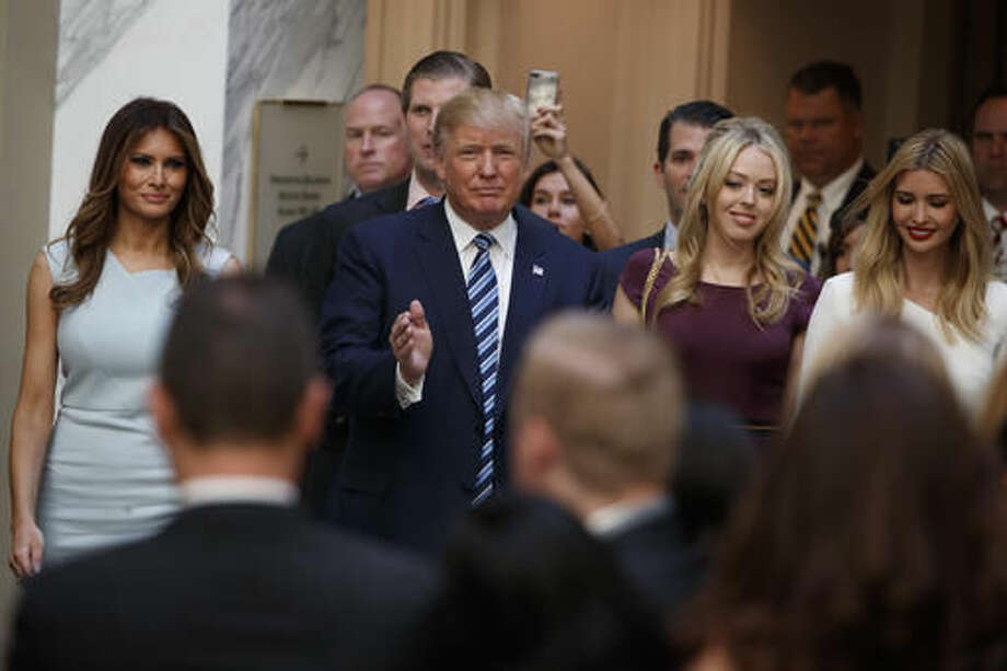Republican presidential candidate Donald Trump, accompanied by, from left, Melania Trump, Eric Trump, Donald Trump Jr., Tiffany Trump and Ivanka Trump, arrives for a ribbon cutting ceremony during the grand opening of the Trump International Hotel- Old Post Office, Wednesday, Oct. 26, 2016, in Washington. (AP Photo/ Evan Vucci)