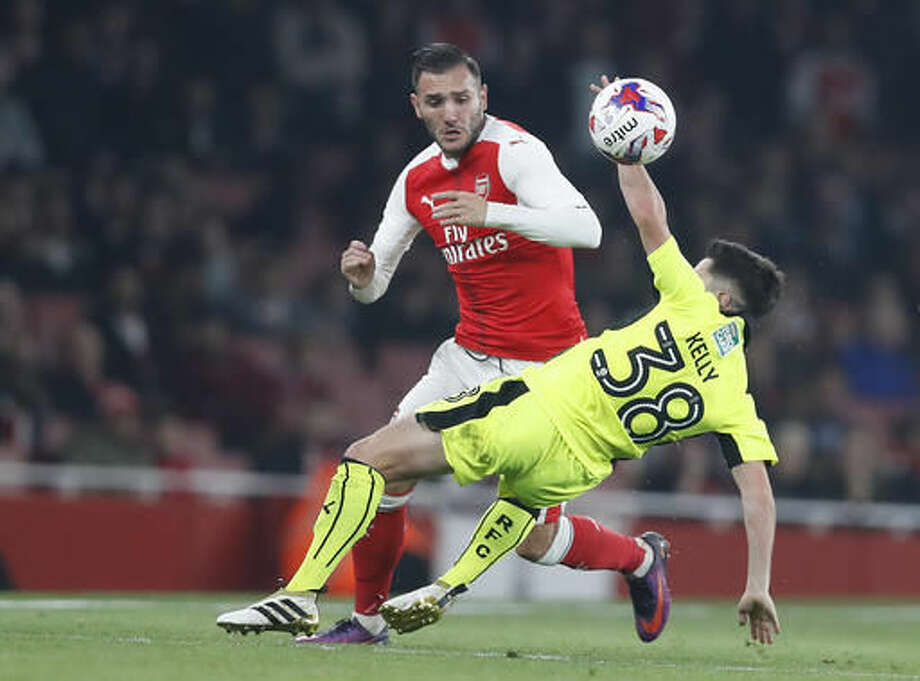 Arsenal's Lucas Perez, left, in action with Reading's Liam Kelly during the English League Cup soccer match between Arsenal and Reading at Emirates stadium in London, Tuesday, Oct. 25, 2016. (AP Photo/Kirsty Wigglesworth)