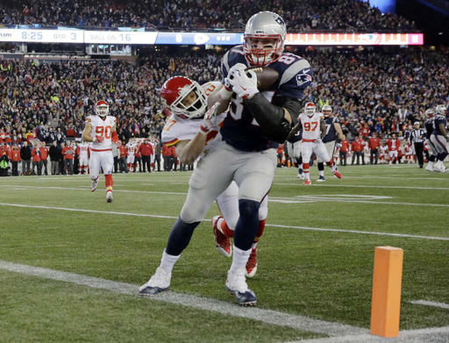 FILE - In this Jan. 16, 2016, file photo, New England Patriots tight end Rob Gronkowski (87) catches a pass for a touchdown ahead of Kansas City Chiefs defensive back Tyvon Branch (27) in the second half of an NFL divisional playoff football game in Foxborough, Mass. Gronkowski is tied with Stanley Morgan for most career touchdowns receiving (67) and career TDs (68) in team history. (AP Photo/Charles Krupa, File)