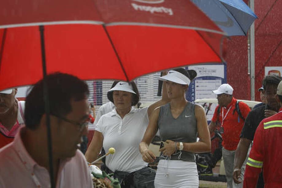 Michelle Wie, center right, of the United States walks in the rain during the second round of the LPGA golf tournament at Tournament Players Club (TPC) in Kuala Lumpur, Malaysia, Friday, Oct. 28, 2016. Round two has been suspended due to weather conditions. (AP Photo/Joshua Paul)