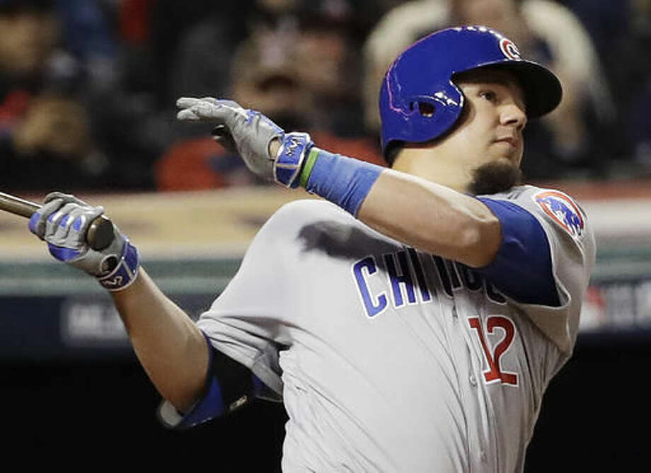 In this Tuesday, Oct. 25, 2016, photo, Chicago Cubs' Kyle Schwarber, wearing a green wristband on his left arm, hits a double during the fourth inning of Game 1 of the Major League Baseball World Series against the Cleveland Indians in Cleveland. Some 1,700 miles away from Wrigley Field, no one is enjoying Schwarber's comeback from a major knee injury more than Campbell Faulkner, a boy with a life-threatening illness, and his family. The 10-year-old Faulkner stays up to watch his buddy in the World Series, and Schwarber proudly wears his Campbell's Crew wristband while he tries to help the Chicago Cubs to their first championship since 1908. (AP Photo/David J. Phillip)