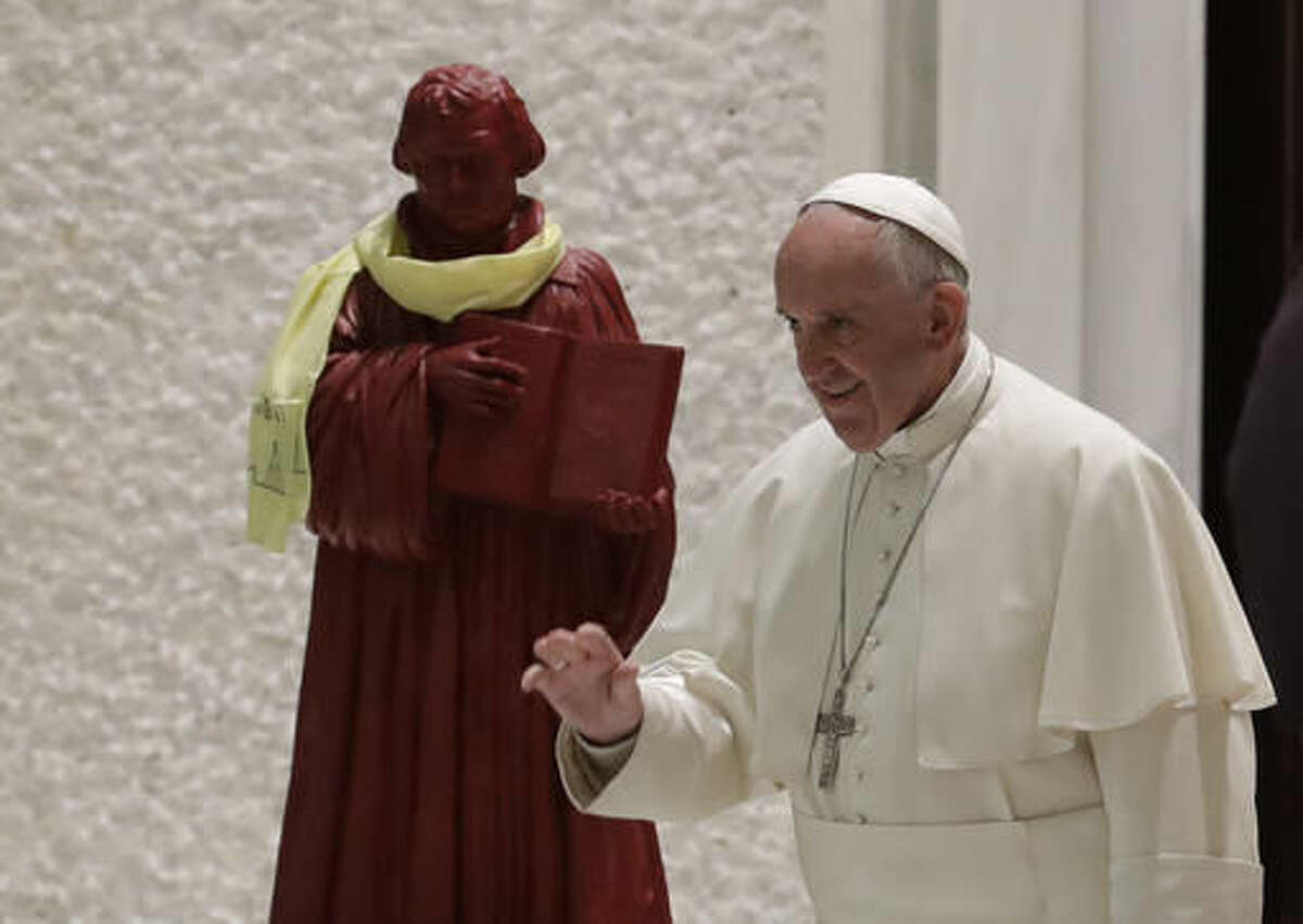 In this photo taken on Oct. 13, 2016, Pope Francis passes by a statue portraying Martin Luther as he arrives for an audience with Lutheran pilgrims at the Vatican. Pope Francis travels to Sweden next week to commemorate the split in Western Christianity 500 years ago. (AP Photo/Alessandra Tarantino)