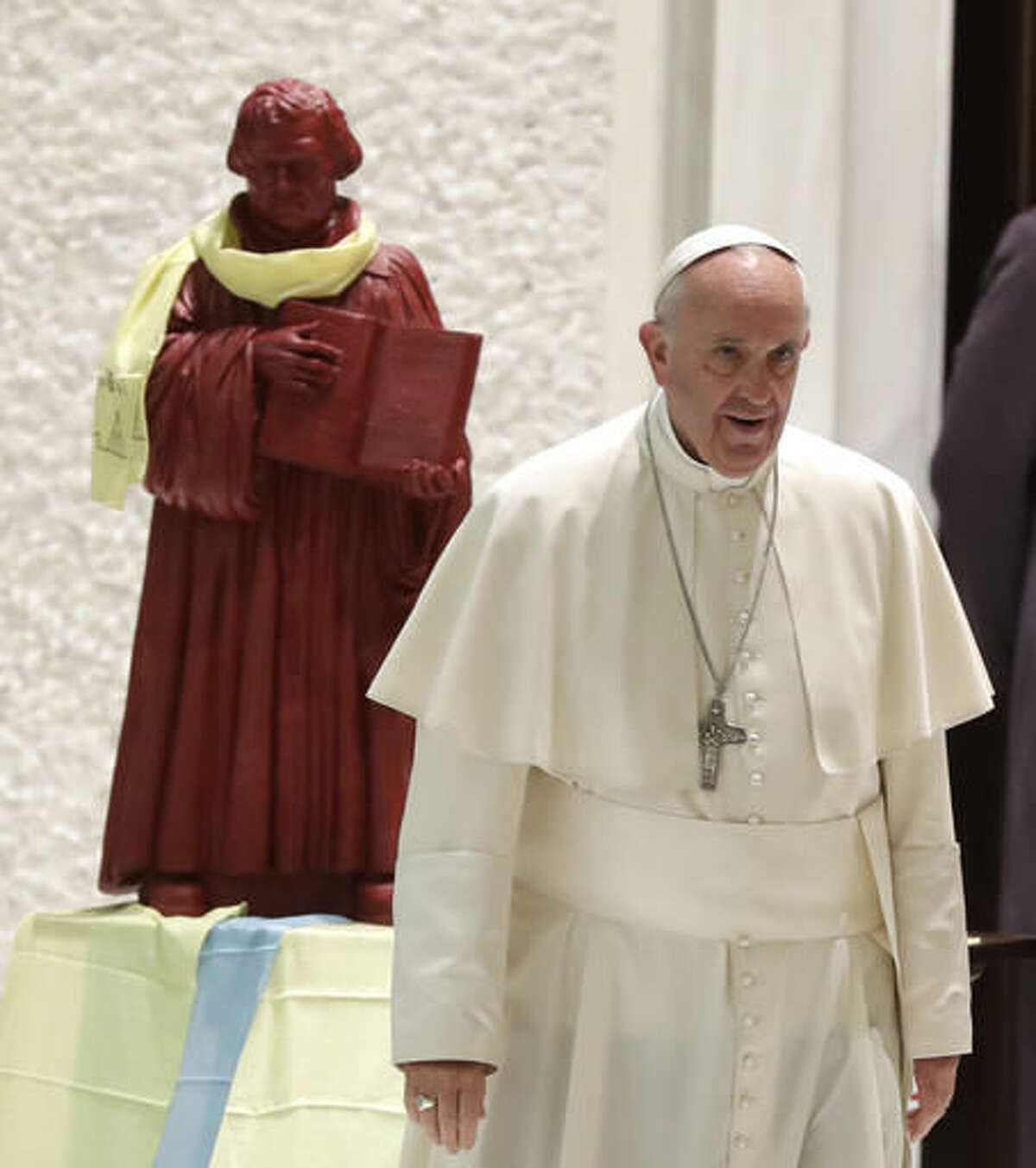 FILE -- In this file photo taken on Oct. 13, 2016, Pope Francis walks by a statue portraying Martin Luther as he arrives for an audience with Lutheran pilgrims at the Vatican. Pope Francis travels to Sweden next week to commemorate the split in Western Christianity 500 years ago. (AP Photo/Alessandra Tarantino)
