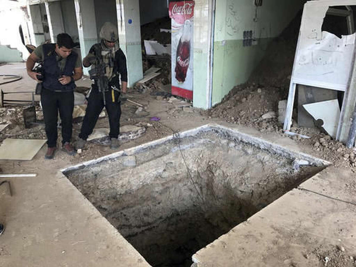 A soldier with Iraq's elite counterterrorism force, left, inspects a tunnel made by Islamic State militants in Bartella, Iraq, Thursday, Oct. 27, 2016. The town of Bartella in northern Iraq lays about 20 kilometres east of Mosul. (AP Photo/Ali Abdul Hassan)