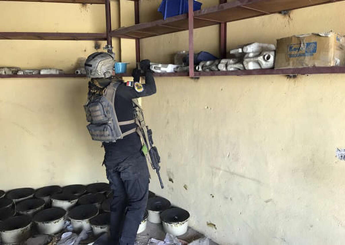 A soldier with Iraq's elite counterterrorism force inspects a building near to a tunnel made by Islamic State militants in Bartella, Iraq, Thursday, Oct. 27, 2016. The town of Bartella in northern Iraq lays about 20 kilometres east of Mosul. (AP Photo/Ali Abdul Hassan)