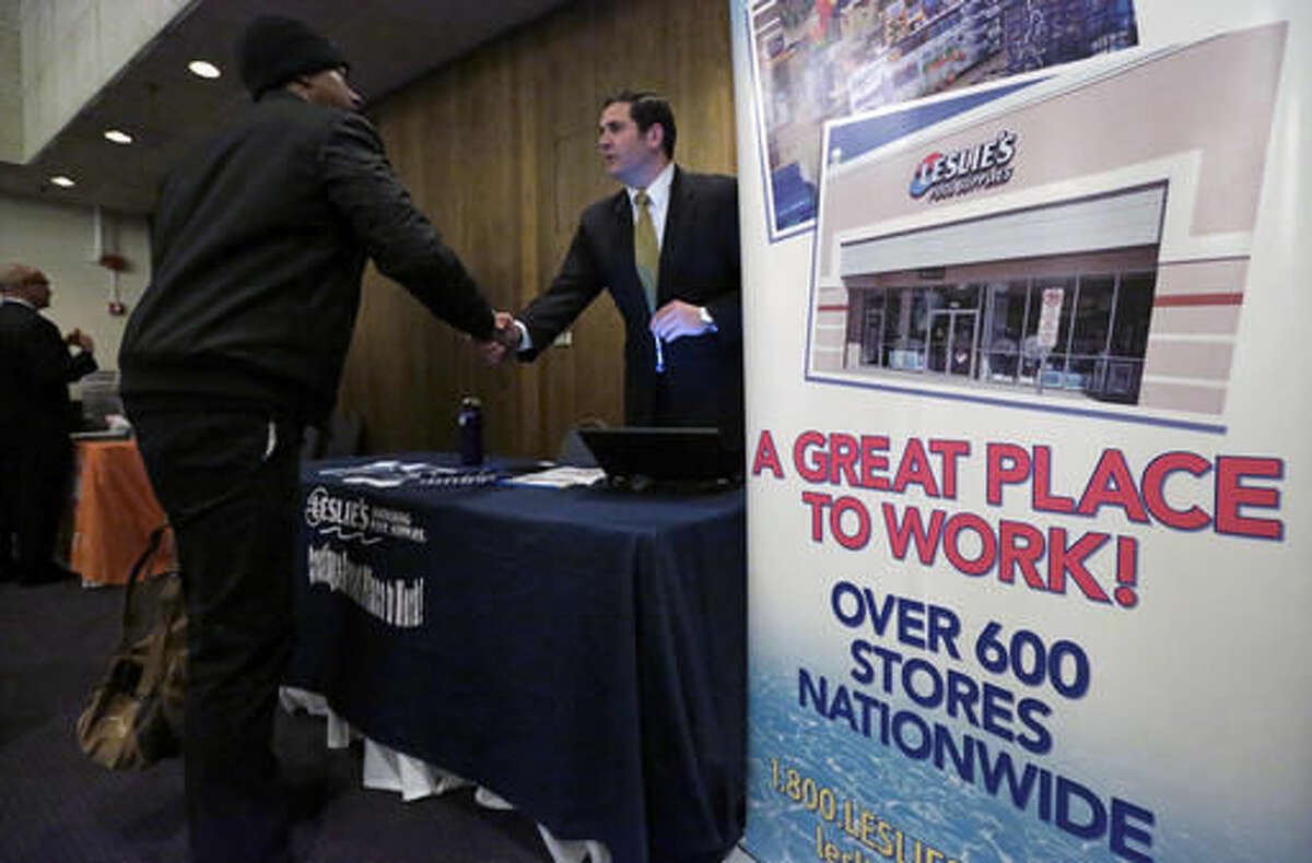 FILE - In this April 22, 2015, file photo, a sign at a recruiting station for Leslie's Pool supplies boasts that it is a great place to work during a National Career Fairs job fair, in Chicago. On Friday, Oct. 28, 2016, the Labor Department releases the employment cost index for the third quarter, a measure of wage and benefit growth. (AP Photo/M. Spencer Green, File)