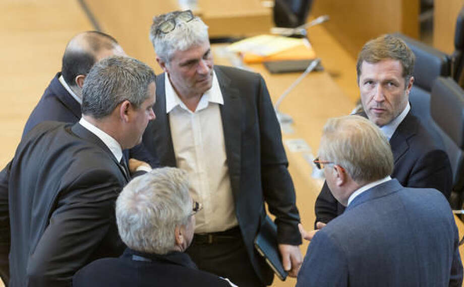 Minister-President of Wallonia Paul Magnette, right, speaks with colleagues during a session in the Walloon Parliament in Namur, Belgium on Friday, Oct. 28, 2016. The European Union and Canada are closing in on a landmark free trade deal after Belgium cleared internal political opposition to the agreement.(AP Photo/Thierry Monasse)
