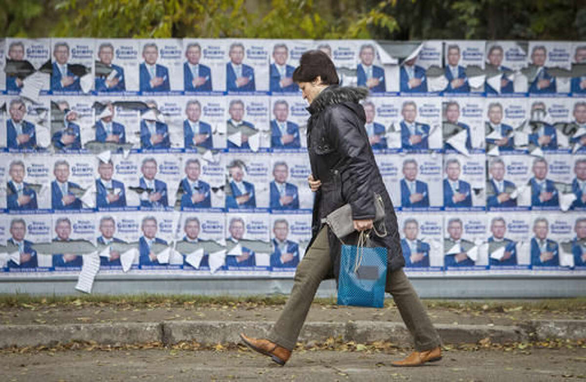 In this picture taken Thursday, Oct. 27, 2016, a woman walks by electoral posters in Chisinau, Moldova. Moldovans will vote for a president Sunday for the first time in 20 years in an election which could move the former Soviet republic closer to Europe or rekindle the nation's old ties with Moscow as both Russia and the West seek greater influence over the strategically placed country of 4 million which signed an association agreement with the EU in 2014.(AP Photo/Roveliu Buga)