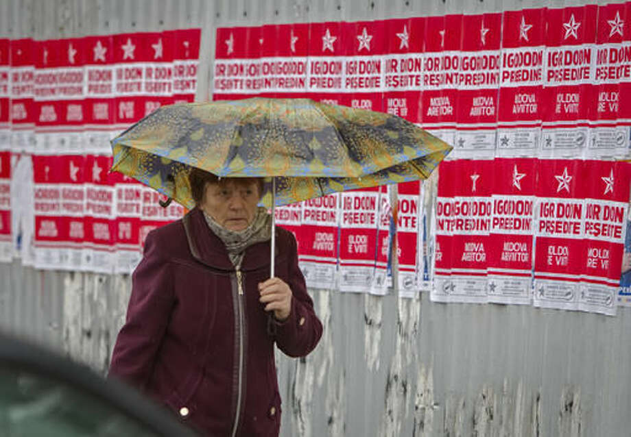 In this picture taken Wednesday, Oct. 26, 2016, a woman walks by electoral posters in Chisinau, Moldova. Moldovans will vote for a president Sunday for the first time in 20 years in an election which could move the former Soviet republic closer to Europe or rekindle the nation's old ties with Moscow as both Russia and the West seek greater influence over the strategically placed country of 4 million which signed an association agreement with the EU in 2014.(AP Photo/Roveliu Buga)