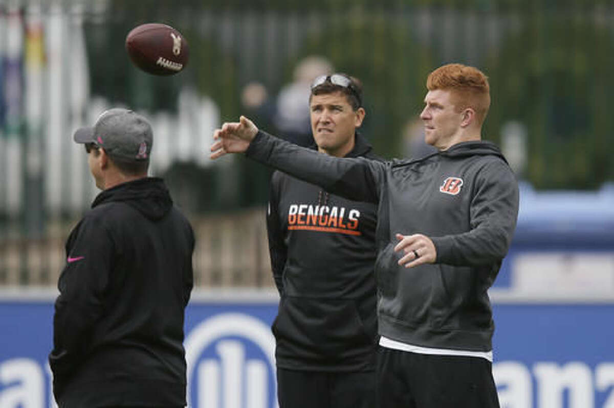 Cincinnati Bengals quarterback Andy Dalton, right, warms up, watched by quarterback coach Bill Lazor, centre, before a practice session at Allianz Park in London, England, Friday Oct. 28, 2016. The Washington Redskins are due to play the Cincinnati Bengals at Wembley Stadium in London on Sunday in a regular season NFL game. (AP Photo/Tim Ireland)