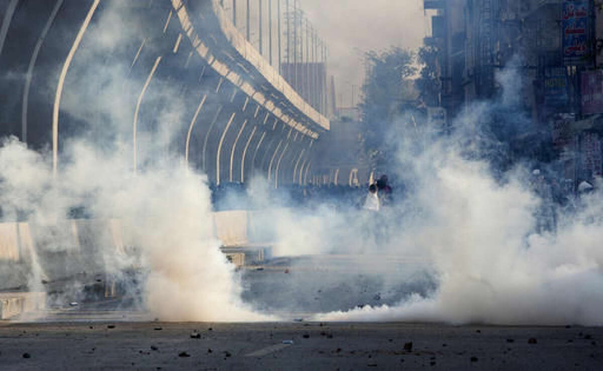 Police fire tear gas to disperse crowd protesting against the government in Rawalpindi, Pakistan, Friday, Oct. 28, 2016. Pakistani police have charged with batons and fired tear gas at stone-throwing supporters of cricketer-turned-politician Imran Khan who are rallying in Islamabad in defiance of a government-imposed ban on demonstrations. (AP Photo/B.K. Bangash)