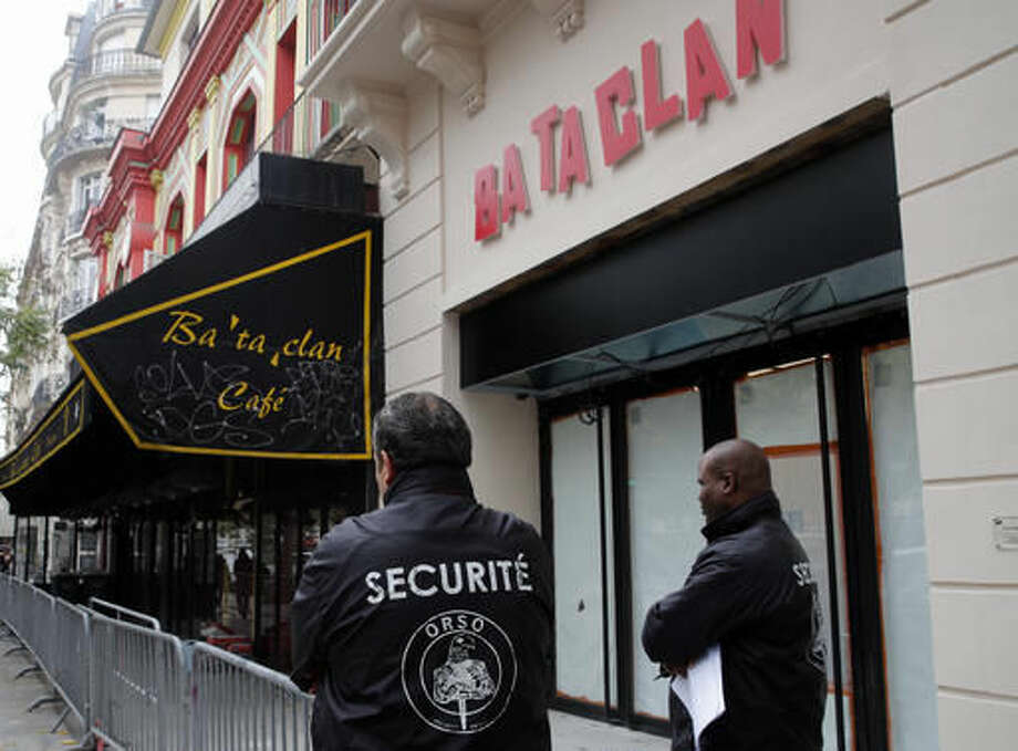 Security guards stands outside the renovated facade of the Bataclan concert hall in Paris, Friday, Oct.28, 2016. The Bataclan concert hall has unveiled its new facade almost one year after being one of the targets of the deadly attacks that killed 130 people in November in Paris. The Bataclan will reopen on Nov. 16 with a performance of British singer Pete Doherty. (AP Photo/Christophe Ena)