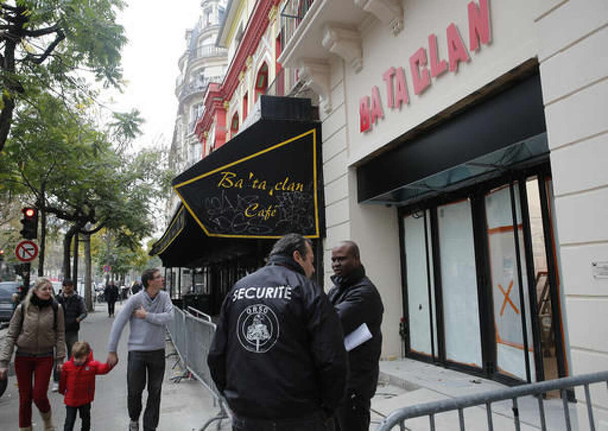 A family walks past the renovated facade of the Bataclan concert hall in Paris, Friday, Oct.28, 2016. The Bataclan concert hall has unveiled its new facade almost one year after being one of the targets of the deadly attacks that killed 130 people in November in Paris. The Bataclan will reopen on Nov. 16 with a performance of British singer Pete Doherty. (AP Photo/Christophe Ena)