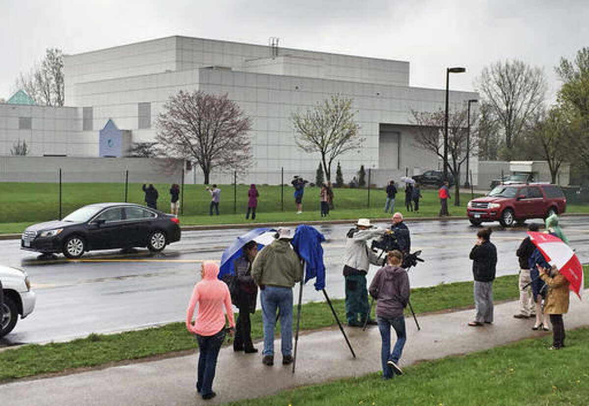 FILE - In this April 21, 2016 file photo, people stand outside the entertainer Prince's Paisley Park compound in Chanhassen, Minn. Following a Chanhassen City Council rezoning vote on Monday, Oct. 24, 2016, Prince's Paisley Park recording studio and home will begin operating as a permanent museum. The museum's website said tours will begin again Friday, Oct. 28. (Jim Gehrz/Star Tribune via AP, File)