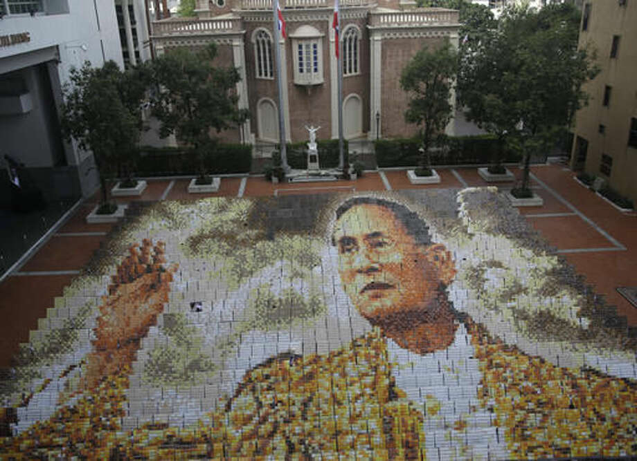A mosaic portrait of the late Thai King Bhumibol Adulyadej is displayed as the 1,250 students practice flipping boards, at Assumption College in Bangkok, Thailand, Friday, Oct. 28, 2016. King Bhumibol died Oct. 13 after reigning for 70 years, plunging the country into grief and extended mourning. The official mourning period is one year. (AP Photo/Sakchai Lalit)