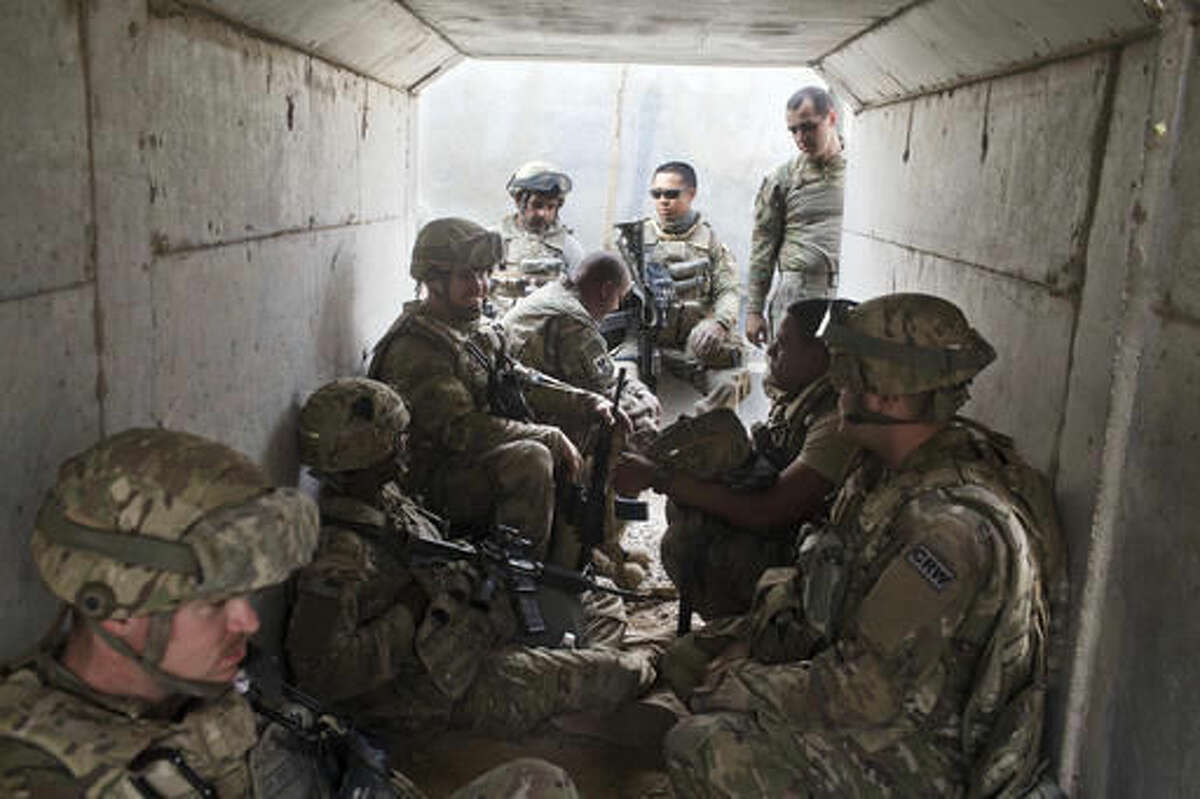"""U.S. military personnel sit in a bunker as an incoming mortar alarm is called at a coalition air base in Qayara, some 50 kilometers south of Mosul, Iraq, Friday, Oct. 28, 2016. The U.S. military says Iraqi forces have retaken 40 villages from the Islamic State group near Mosul since a massive operation to drive the militants from the city began last week. It says Iraqi troops are consolidating gains made east and south of the city earlier this week, but insisted """"momentum"""" was still on their side. (AP Photo/Marko Drobnjakovic)"""