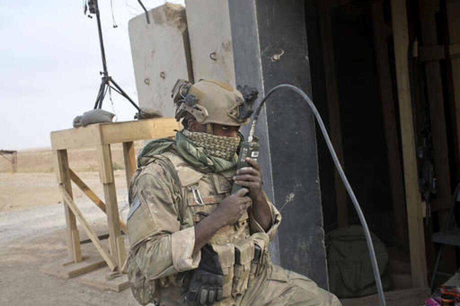 """U.S. Air Force service member Dennis Marshall, 26, from Memphis, Tenn., uses his radio at a coalition air base in Qayara, some 50 kilometers south of Mosul, Iraq, Friday, Oct. 28, 2016. The U.S. military says Iraqi forces have retaken 40 villages from the Islamic State group near Mosul since a massive operation to drive the militants from the city began last week. It says Iraqi troops are consolidating gains made east and south of the city earlier this week, but insisted """"momentum"""" was still on their side. (AP Photo/Marko Drobnjakovic)"""