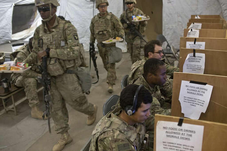 """U.S. service members, including soldiers from the Army's 101st Airborne Division use computers and prepare to eat inside a tent at at a coalition air base in Qayara, some 50 kilometers south of Mosul, Iraq, Friday, Oct. 28, 2016. The U.S. military says Iraqi forces have retaken 40 villages from the Islamic State group near Mosul since a massive operation to drive the militants from the city began last week. It says Iraqi troops are consolidating gains made east and south of the city earlier this week, but insisted """"momentum"""" was still on their side. (AP Photo/Marko Drobnjakovic)"""