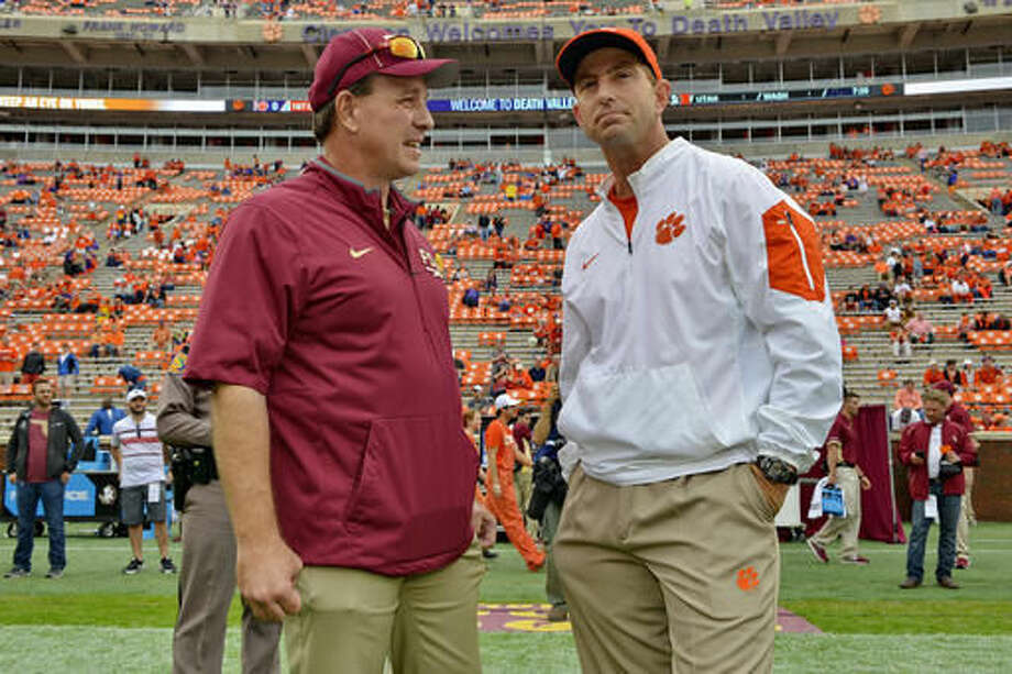 FILE - In this Nov. 7, 2015, file photo, Florida State head coach Jimbo Fisher, left, and Clemson head coach Dabo Swinney talk before the start of an NCAA college football game in Clemson, S.C. Another Clemson-Florida State matchup in the Top 25, another challenge for Wake Forest¹s tough run defense and a reason to think Duke can upset Georgia Tech headline Week 9 around the Atlantic Coast Conference. (AP Photo/Richard Shiro, File)