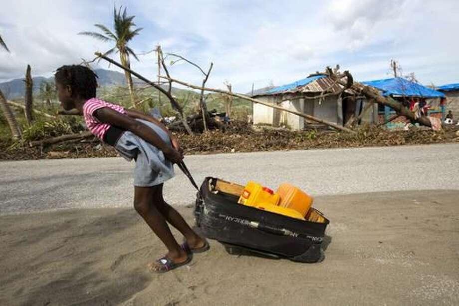 In this Oct. 25, 2016 photo, a girl drags a suitcase of containers full of fresh water in Aux Coteaux, a district of Les Cayes, Haiti. The girl found the suitcase in debris left behind by Hurricane Matthew. (AP Photo/Dieu Nalio Chery)