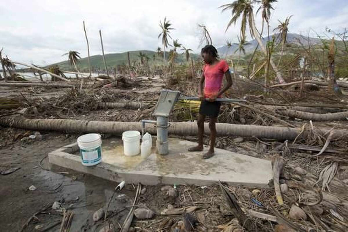 In this Oct. 25, 2016 photo, Gelene Jeudy, 16, pumps water from a contaminated well in Aux Coteaux, a district of Les Cayes, Haiti. In parts of the city of Les Cayes, people could be seen drinking straight from a contaminated well, bypassing treated supplies set up by South Carolina-based organization known as Water Mission. (AP Photo/Dieu Nalio Chery)