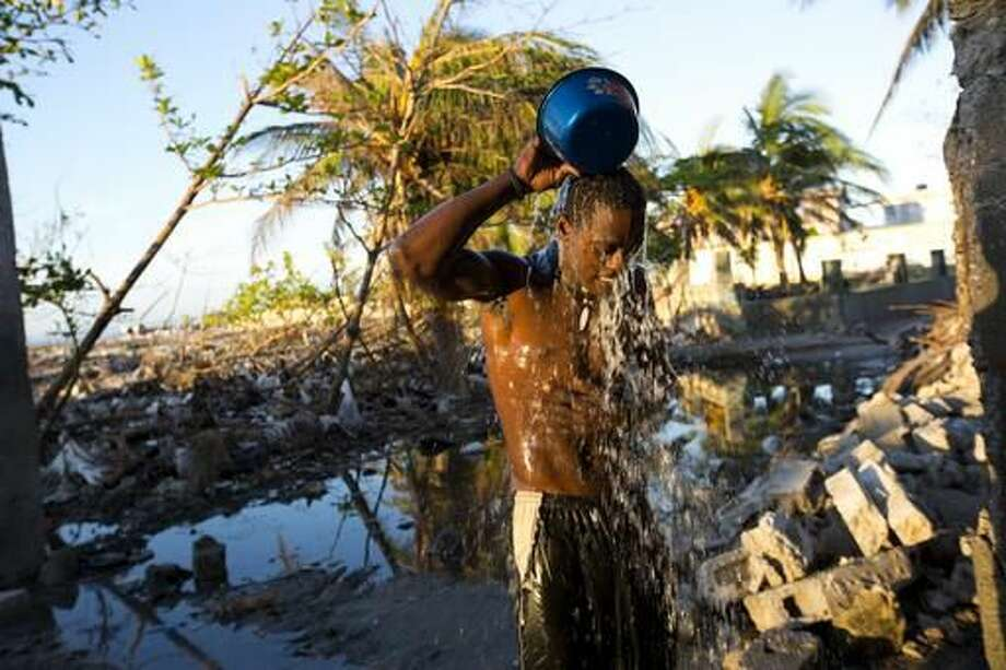 In this Oct. 25, 2016 photo, Makenley Alcide bathes with fresh well water in Les Cayes, Haiti. Public services in general were shabby before Hurricane Matthew. Portions of some coastal towns in the southwest have gained piped water networks in recent years, though there is no sewage treatment in the area. (AP Photo/Dieu Nalio Chery)