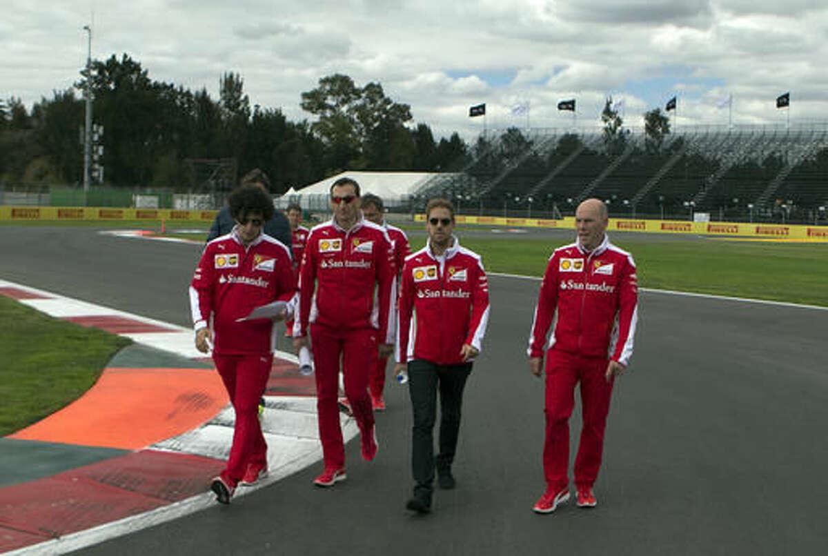 Scuderia Ferrari driver Sebastian Vettel, second right, walks with teammates on the Hermanos Rodriguez racetrack as they inspect the course ahead of the Formula One Mexico Grand Prix, in Mexico City, Thursday, Oct. 27, 2016. (AP Photo/Eduardo Verdugo)