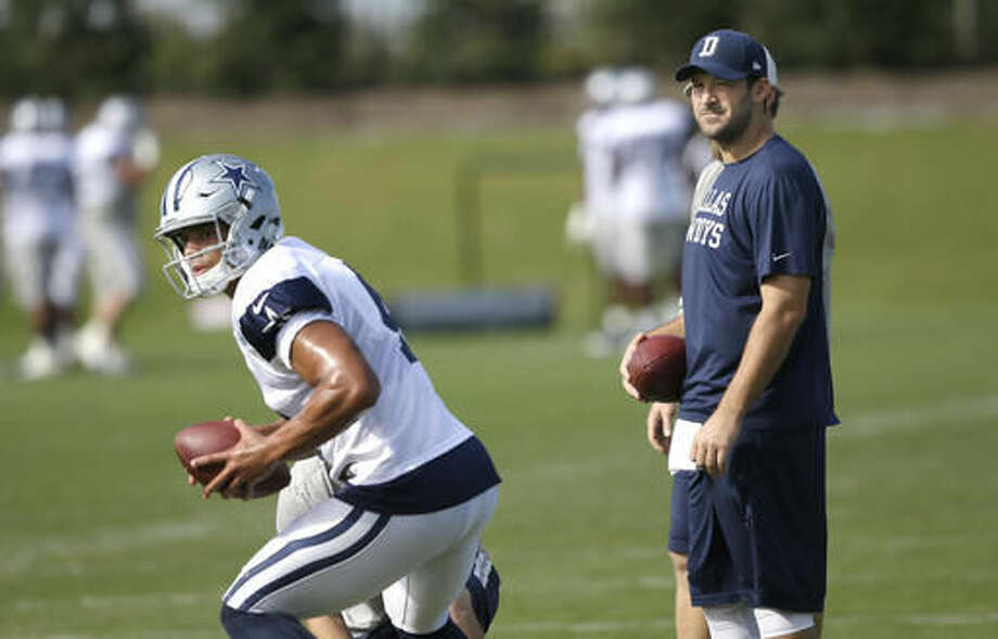 Dallas Cowboys quarterback Tony Romo looks on as fellow quarterback Dak Prescott runs a drill during NFL football practice at the team's practice facility in Frisco, Texas, Wednesday, Oct. 26, 2016. (AP Photo/LM Otero)
