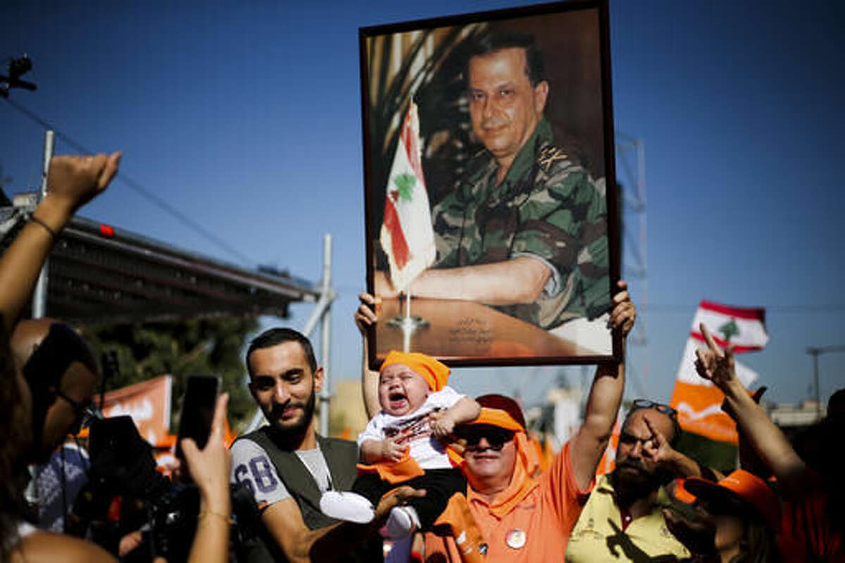 FILE - In this Sunday Oct. 16, 2016 file photo, supporters of Christian leader Michel Aoun hold his picture and Free Patriotic Movement Party and Lebanese flags, as a man holds up a baby while posing for a picture during a rally near the presidential palace in the Beirut suburb of Baabda, Lebanon. Michel Aoun, an 81-year-old veteran Christian leader, is set to be elected by Parliament on Monday as part of a political deal that's expected to be another boost for President Bashar Assad in neighboring Syria. (AP Photo/Hassan Ammar, File)