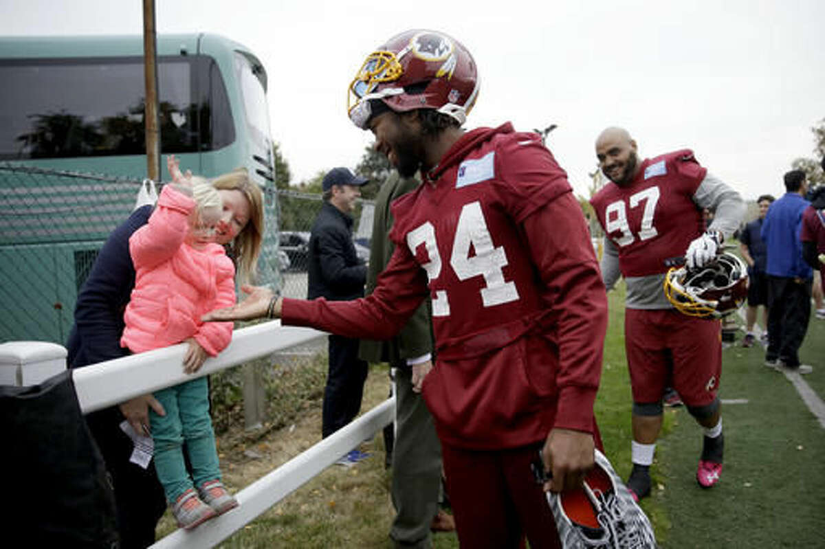 Washington Redskins' cornerback Josh Norman, 24, who is recovering from a concussion, high-fives a little girl after a training session at Wasps rugby union team training ground in west London, Friday, Oct. 28, 2016. The Washington Redskins are due to play the Cincinnati Bengals at Wembley stadium in London on Sunday in a regular season NFL game. (AP Photo/Matt Dunham)
