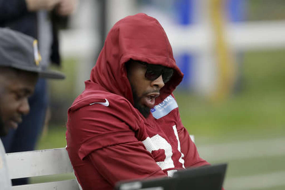 Washington Redskins' cornerback Josh Norman, who is recovering from a concussion, yawns as he sits on a bench at the start of a training session at Wasps rugby union team training ground in west London, Friday, Oct. 28, 2016. The Washington Redskins are due to play the Cincinnati Bengals at Wembley stadium in London on Sunday in a regular season NFL game. (AP Photo/Matt Dunham)