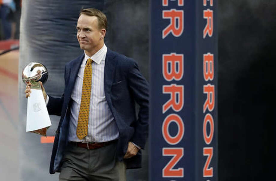 FILE - In this Sept. 8, 2016, file photo, former Denver Broncos quarterback Peyton Manning carries the Vince Lombardi Trophy from Super Bowl 50 onto the field prior to an NFL football game against the Carolina Panthers in Denver. Manning has gone to TV commercials full time. Adrian Peterson and J.J. Watt are injured. Aaron Rodgers is struggling. Too many of the NFL's headline grabbers aren't in the news, or aren't producing the kind of plays and drama football fans crave. (AP Photo/Jack Dempsey, File)