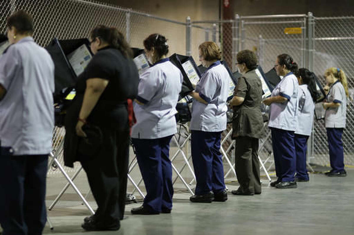 In this Oct. 26, 2016, photo, casino workers vote at an early voting site in Las Vegas. Inflamed by Trump's candidacy but with an eye on turning the whole ticket blue, organized labor groups including the heavily immigrant Culinary Union are in the thick of an aggressive get-out-the-vote campaign in Nevada. (AP Photo/John Locher)
