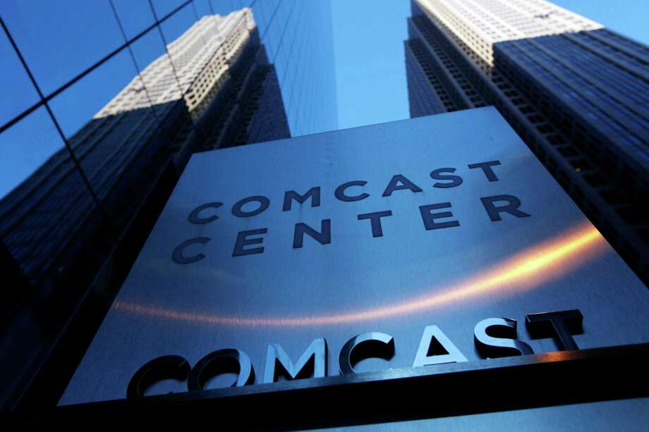 FILE - In this Dec. 3, 2009, file photo, a sign outside the Comcast Center is seen in Philadelphia. Under a President Donald Trump, cable and phone companies could gain new power to influence what you do and what you watch online, not to mention how much privacy you have while you're at it. During the campaign, Trump spoke out several times against media giants and that he might look at breaking up Comcast and NBCUniversal. But some analysts think that with Republicans in charge of agencies like the Federal Communications Commission and the Department of Justice, mergers are more likely to sail through. Photo: Matt Rourke, AP / AP