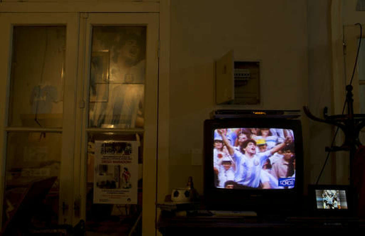 A television set shows 1986 footage of soccer legend Diego Armando Maradona celebrating his teams win of the World Cup in Mexico, inside his former home in Buenos Aires, Argentina, Thursday, Oct. 27, 2016. The home where Maradona lived as a teenager while playing for Argentinos Juniors recently opened to the public, becoming a new shrine for the soccer legend. (AP Photo/Natacha Pisarenko)