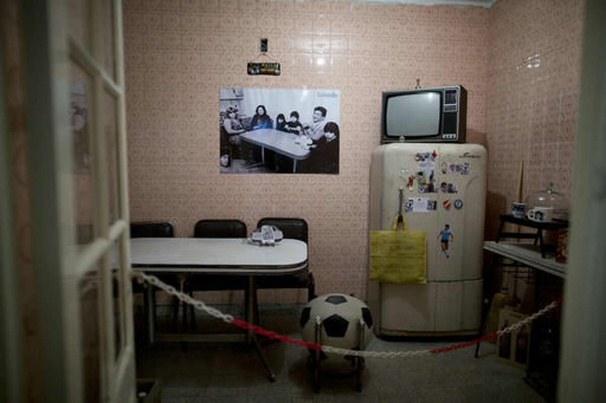 A photograph of Diego Armando Maradona's family hangs inside the kitchen of his old home in Buenos Aires, Argentina, Thursday, Oct. 27, 2016. The home where Maradona lived as a teenager while playing for Argentinos Juniors recently opened to the public, becoming a new shrine for the soccer legend. (AP Photo/Natacha Pisarenko)